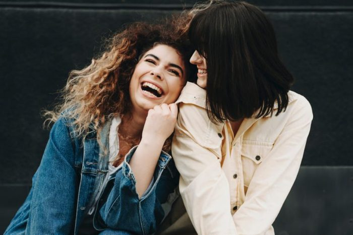 Portrait of two attractive girls dressed in jeans blue and yellow jackets having fun and laughing against a black wall.