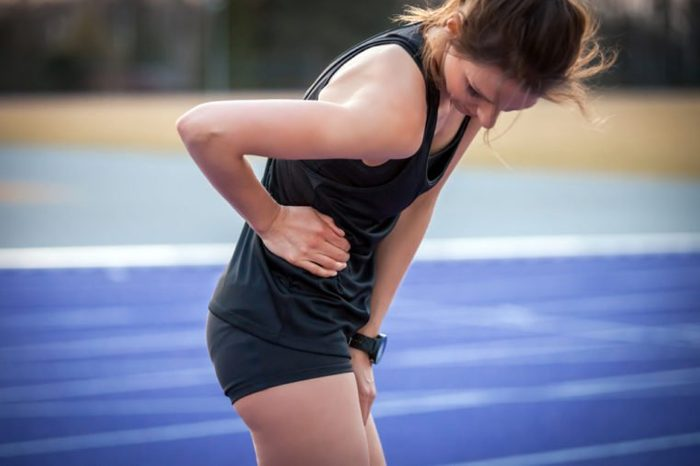 Athlete woman has side crumps, pain during running training