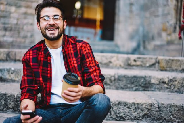 Excited handsome man in casual wear satisfied with tariffs for mobile internet in roaming sitting on street, cheerful hipster guy laughing on funny message get on cellular mail holding coffee to go