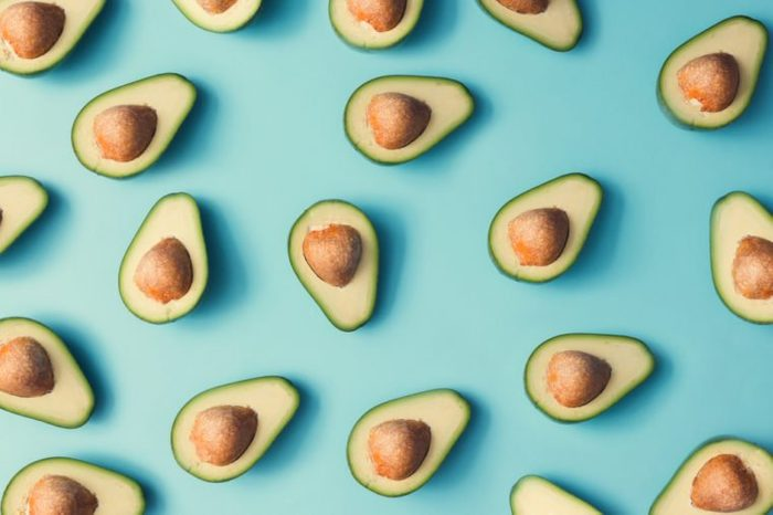 Avocado colorful pattern on a pastel blue background. Summer concept. Flat lay.