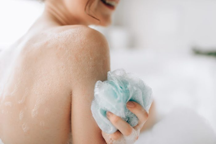 Female person soaps the body with a sponge