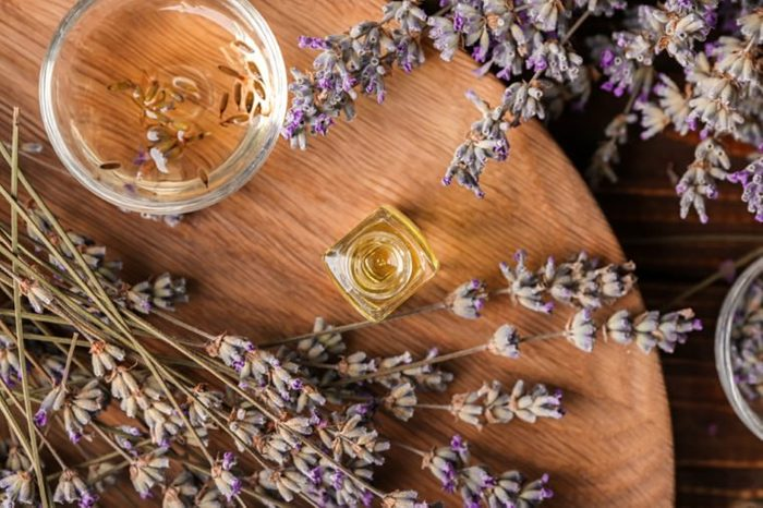 Glassware with essential oil and lavender on wooden board
