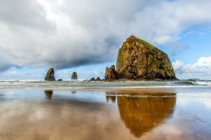Oregon coast scenic Haystack Rock on a dramatic day with clouds and reflections. Famous destination for bird watchers.