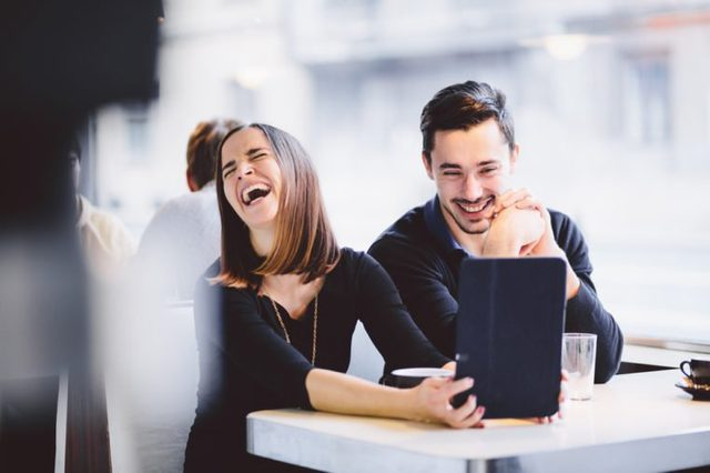 Young couple looking at photos on tablet computer laughing