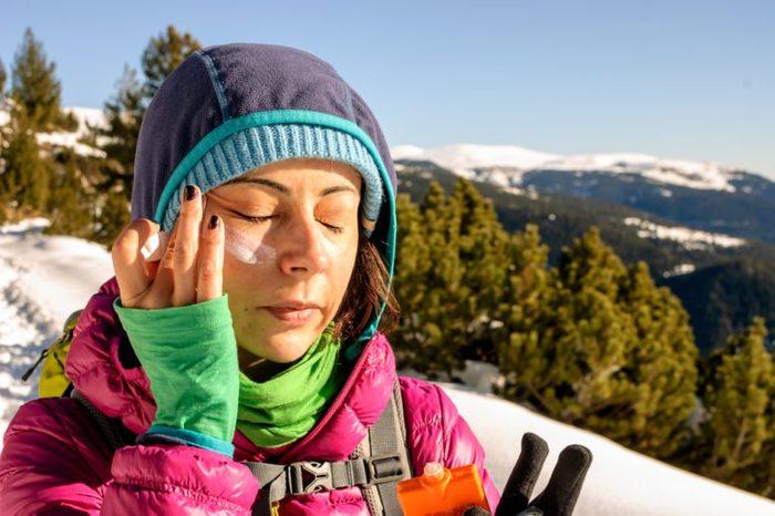 Woman using sunscreen.