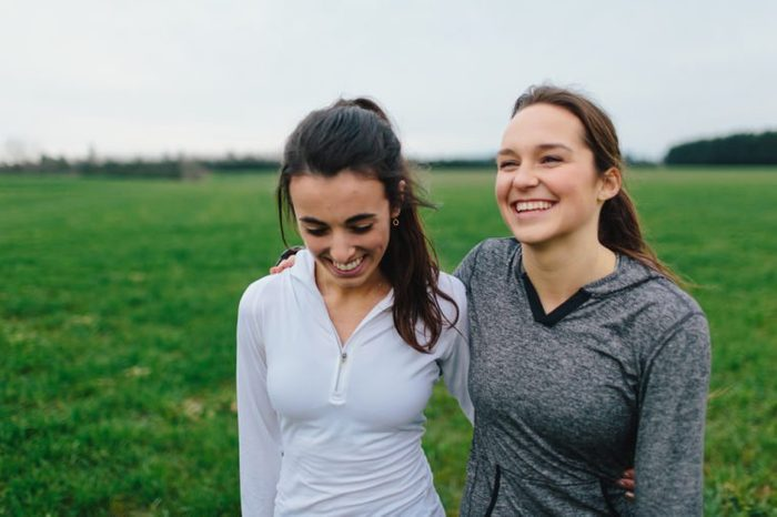 Young Adult Female Runners Arms Around each other smiling in country field