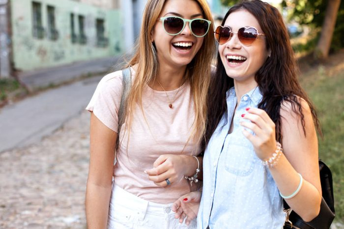 Two cheerful girls in sunglasses having fun and walking on street