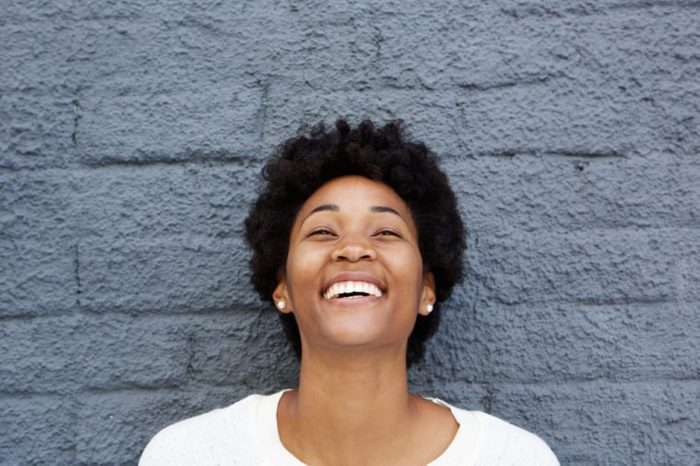 Closeup portrait of beautiful african young woman laughing against grey wall