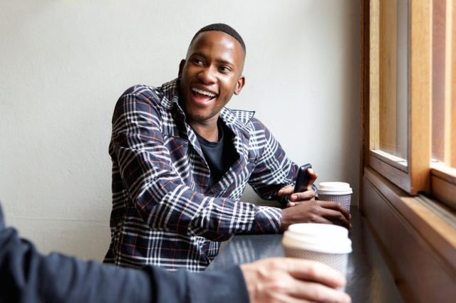Portrait of smiling young african man sitting at cafe with a friend