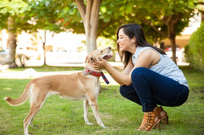 Profile view of a beautiful young woman petting her dog and giving it a kiss at a park
