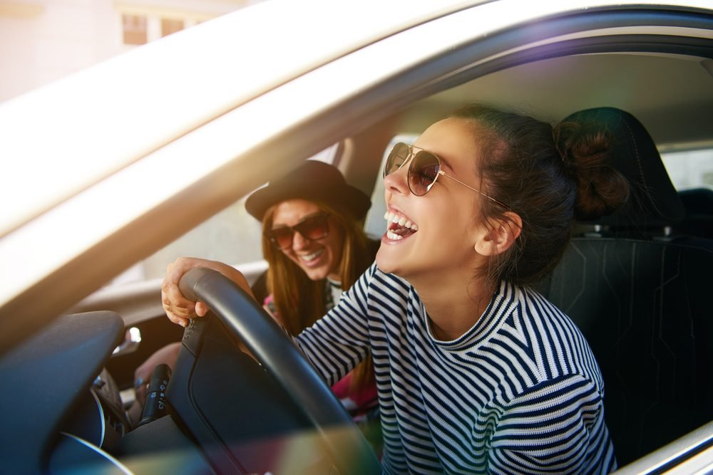 Laughing young woman wearing sunglasses driving a car with her girl friend , close up profile view through the open window
