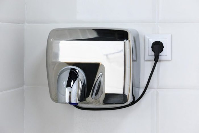 Metal hand dryer on the white tiled wall