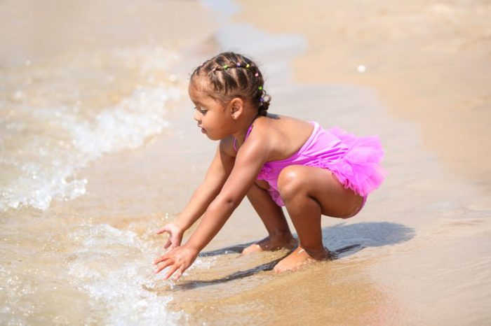 Happy young girl playing in the waves