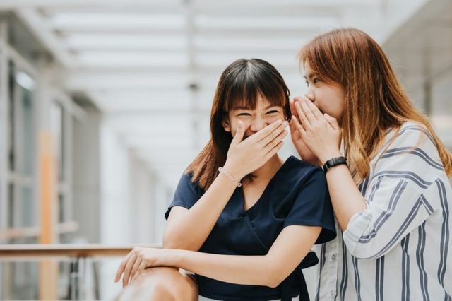 Young Asian girl whispering gossip or secret to her friend with smile and laugh