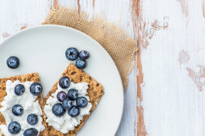 Healthy Snack from Wholegrain Rye Crispbread Crackers with Ricotta Cheese and Fresh Blueberries on the Light Background