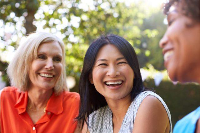 Mature Female Friends Socializing In Backyard Together