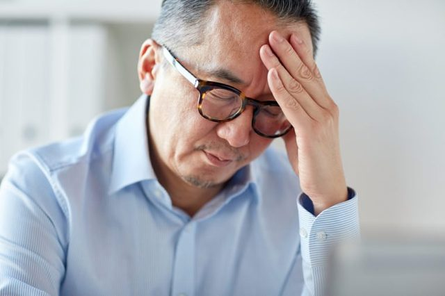 business, overwork, stress, deadline and people concept - close up of tired businessman in eyeglasses suffering from headache at office