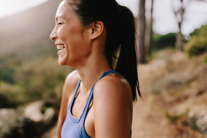 Side view shot of fit young woman standing outdoors, looking away and laughing. Happy female runner in sportswear in morning.