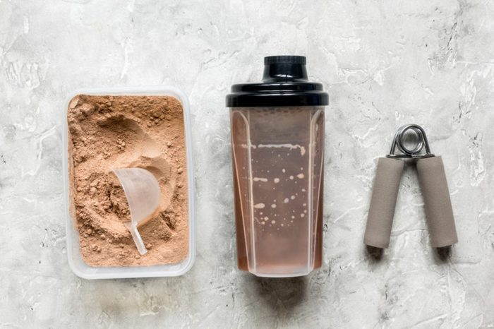 Fitness nutrition with shaker, bars on stone background top view