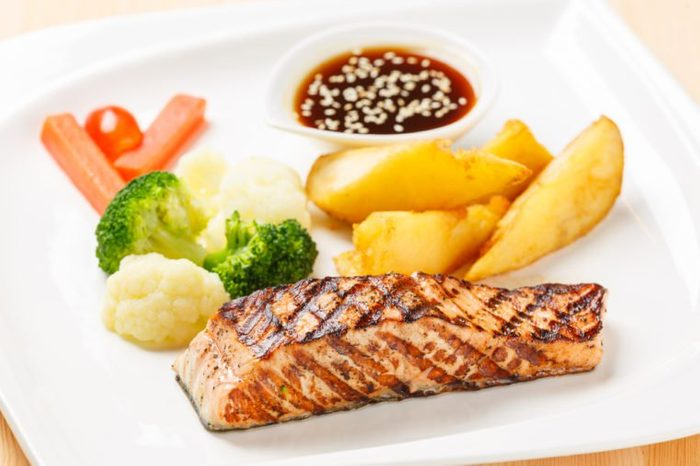 Salmon grilled steak served with fried potato carrot, broccoli, cauliflower, sweet sauce and white sesame in ceramic dish on wooden table