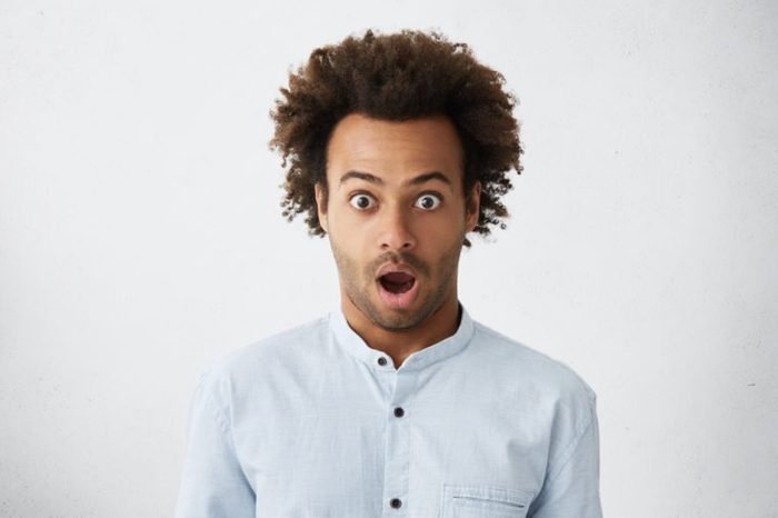 Studio portrait of bug-eyed dark-skinned man with bushy dark hair and bristle looking with surprise unexpecting to hear news. Scared man with wide opened eyes and mouth isolated over white wall