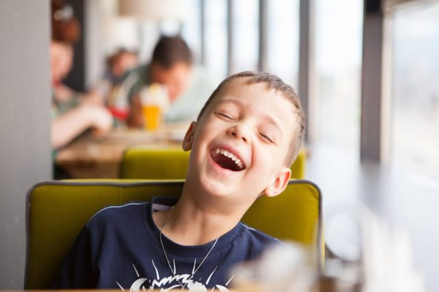 boy is laughing loudly in cafe