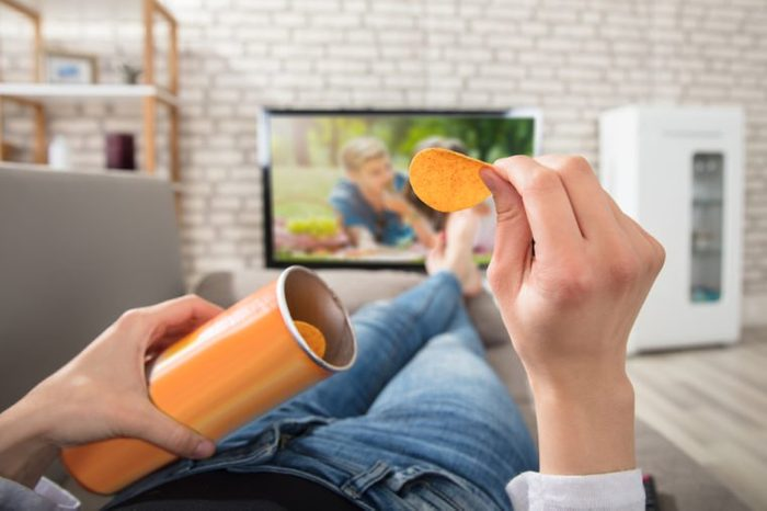Close-up Of A Woman Eating Potato Chips While Watching Television