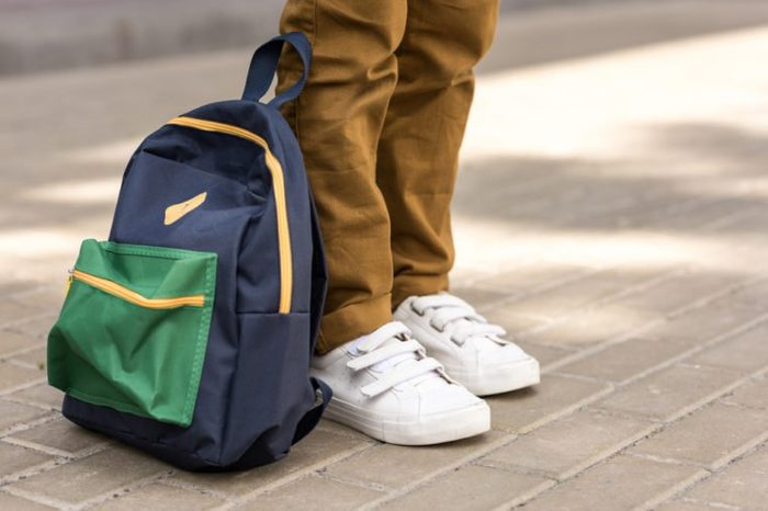 cropped shot of stylish schoolboy standing with backpack on street