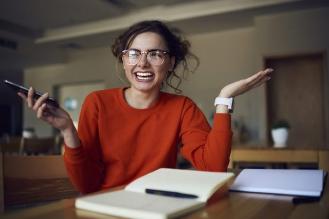 Portrait of cheerful female student laughing sitting in library satisfied with completing coursework making creative solution, smiling hipster girl received message with good advertising offer