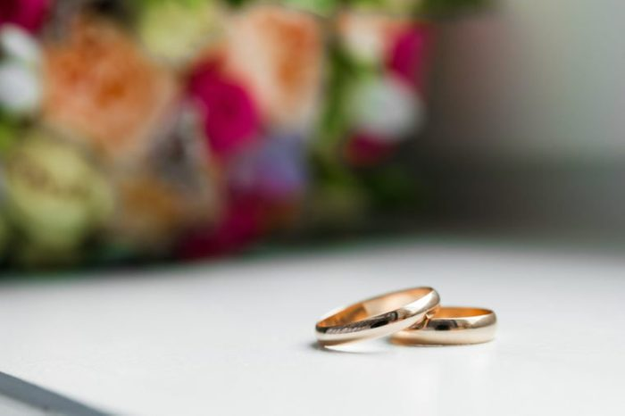Gold wedding rings on the wedding bouquet of the bride