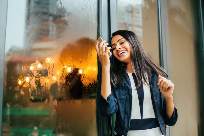 A happy young Indian woman looking in her phone and laughing