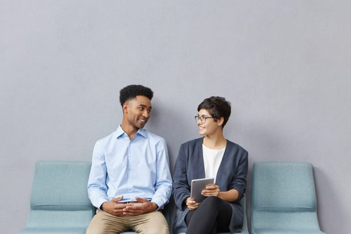 Candid shot of positive young African man and Caucasian woman job candidates wearing formal clothes sitting in queue on chairs in waiting room for a long time, talking and amusing themselves