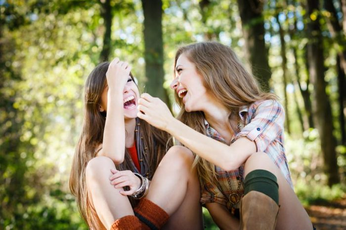 two young beautiful females laughing talking having good time sitting in park