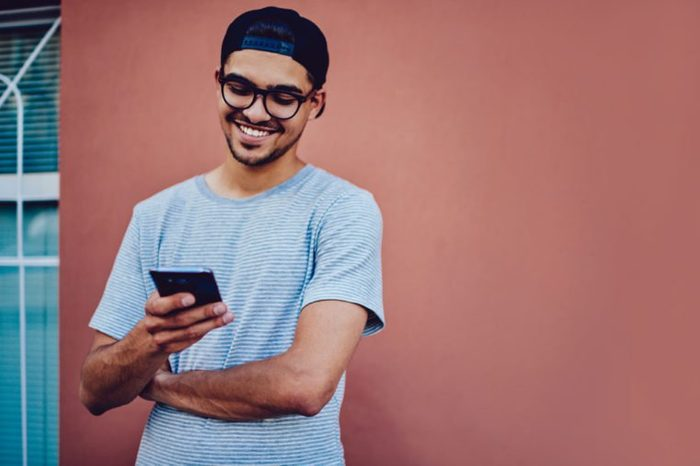 Cheerful young man in trendy baseball cap watching funny video on mobile phone using 4G connection, smiling hipster guy reading good news from networks standing on wall promotional background