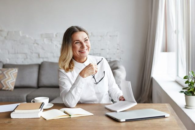 Experienced mature female chief editor holding glasses in one hand and book in other, laughing at sarcastic style of narration while reading novel of popular author. Writing and publishing concept