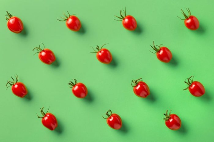 Colorful pattern of red tomatos on green background. From top view