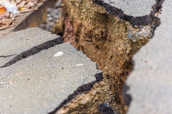 Asphalt road cracked and broken from earthquake, Louangphabang, Laos. Close-up