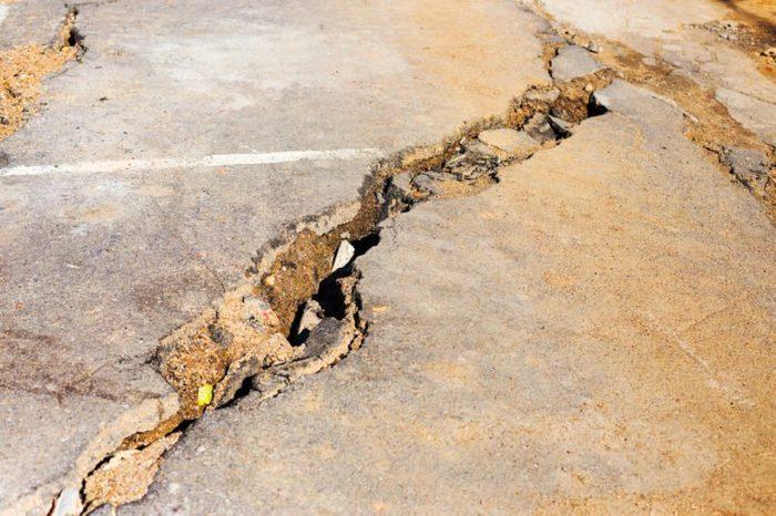 Huge cracks on pavement due to natural disasters, landslide, earthquake. Broken coating of asphalt leading to pothole, dangerous for vehicles pedestrians. Of poor road emergency situations