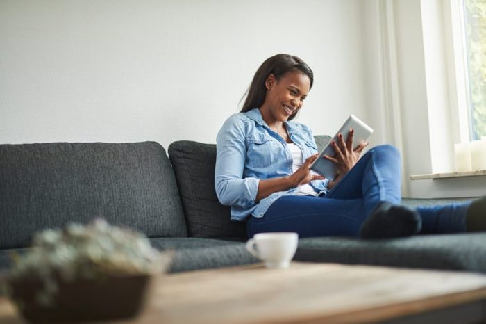 Young African woman laughing while relaxing on her living room sofa browsing online with a digital tablet