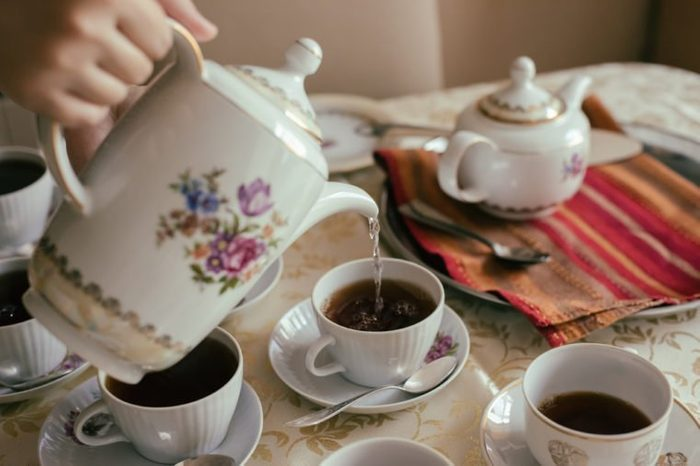 Teapot and cups with tea on table, tea drinking