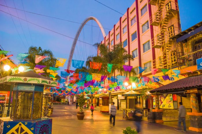 TIJUANA, MEXICO - APRIL 26, 2017: Santiago Arguello pedestrianized shopping and bars street with festival flags above, millennial arch (el arco y reloj monumental) and blurred motion silhuettes