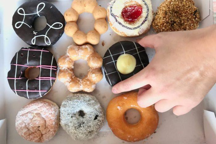 a man's hand reaching to grab a piece of doughnut.