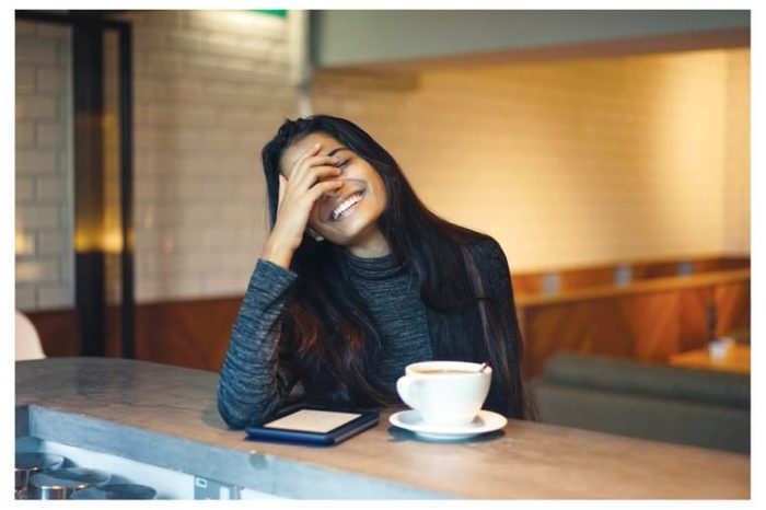 Portrait of a young, attractive and elegant Indian Asian lady in a warm and cosy cafe. She is laughing in a natural, relaxed manner.