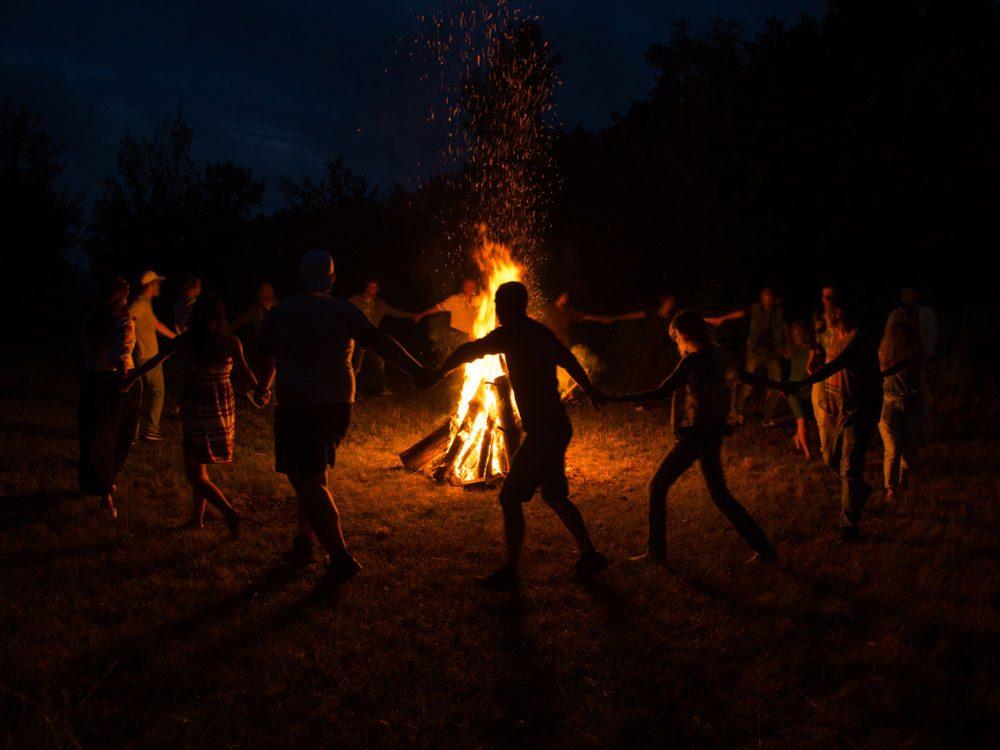 Group dance around giant bonfire