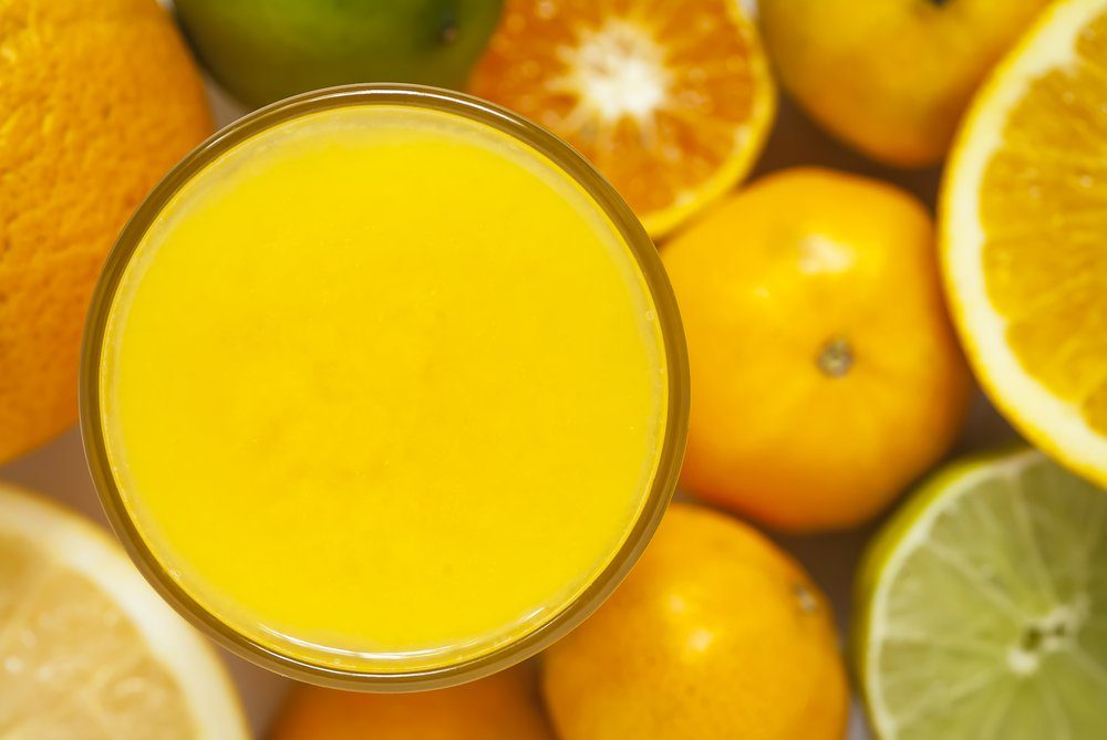 An overhead image of a glass with citrus juice, surrounded by citrus fruit.