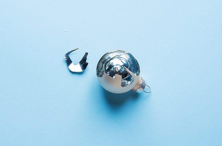 Broken Christmas Tree Ornament Ball on Blue Background. Splinters Glittering. Luck Hope Concept. Superstition.
