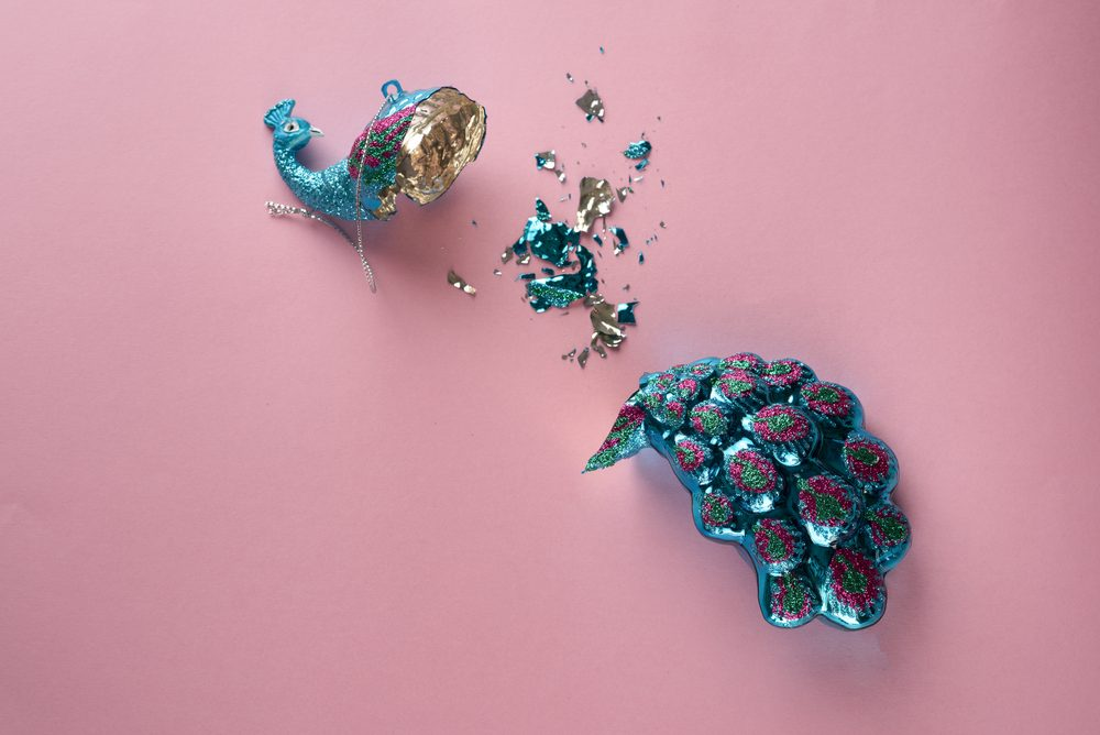 Broken Christmas Toy. Crashed bauble. Damages Gorgeous glass peacock on pink background.