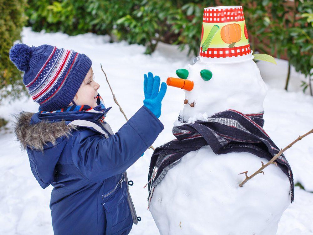 Kid decorating snowman