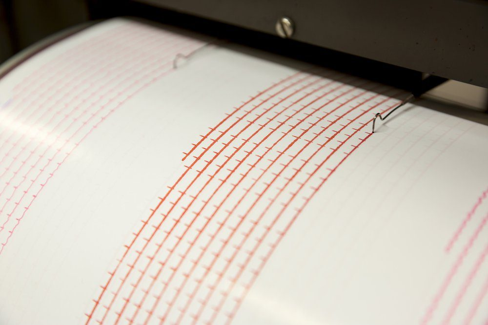 Seismograph records an earthquake on the sheet of measuring paper. Seismological device for measuring earthquakes. Seismograph machine needle drawing a red line on graph paper measuring activity.