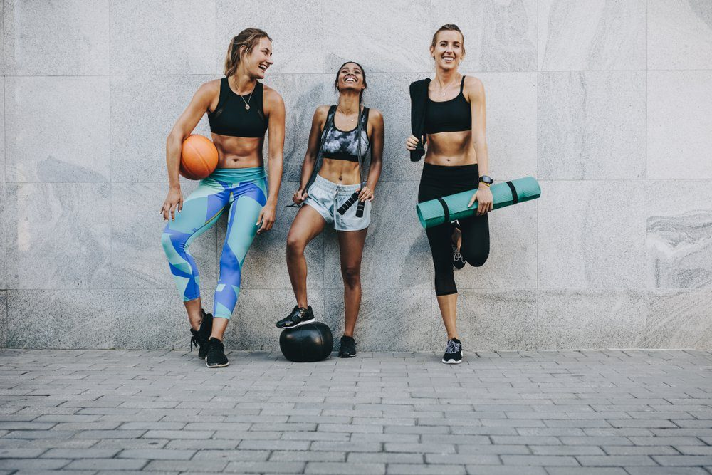 Happy fitness women standing outdoors against a wall holding basketball skipping rope and exercise mat. Fitness women having fun standing on street after workout.